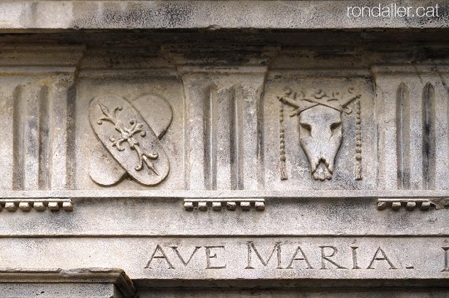 Capella del Remei de Caldes de Montbui. Fris damunt la porta amb uns escut i un crani de bou.