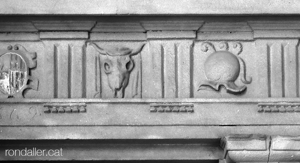 Fris amb triglifs i metopes decorades amb un escut, un crani de bou i un elm a l'Hospital de la Santa Creu de Barcelona.