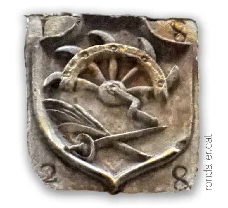 Carrer Freixures de Barcelona. Detall d'un escut amb els símbols del martiri de Santa Caterina.