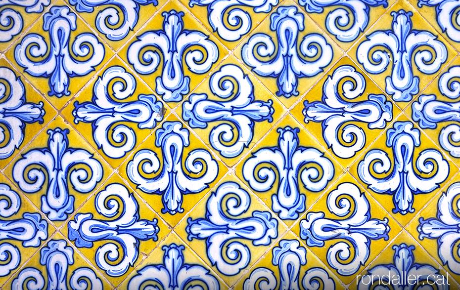 Enrajolat de la façana del Mercat Central amb un motiu repetitiu sobre fons groc. Rajola de València