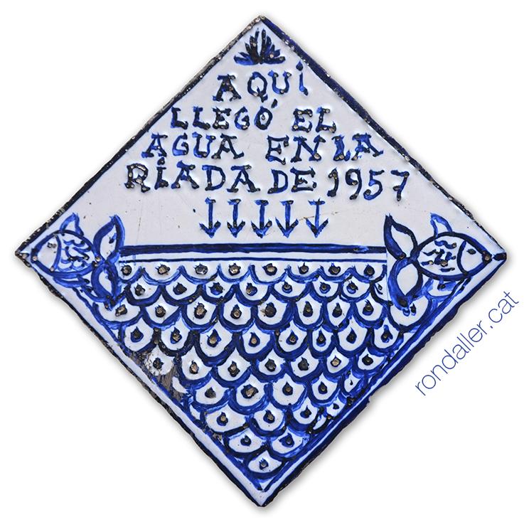 Rajola romboïdal pintada de color blau, commemorativa del desbordament del riu Túria el 1957.