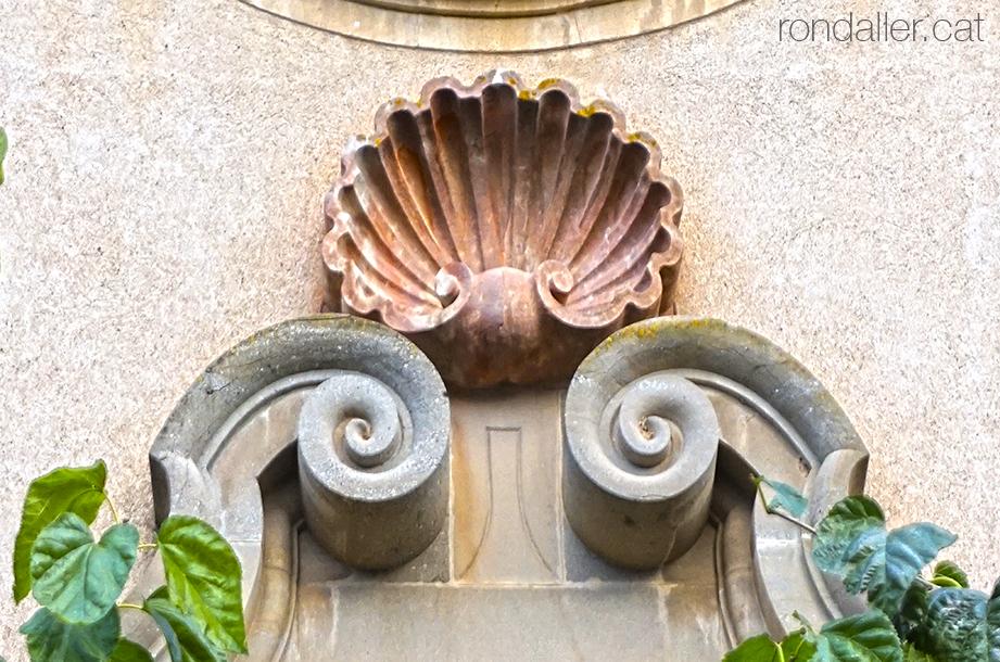 Una gran petxina o venera presidint la portalada neobarroca de l'església parroquial.