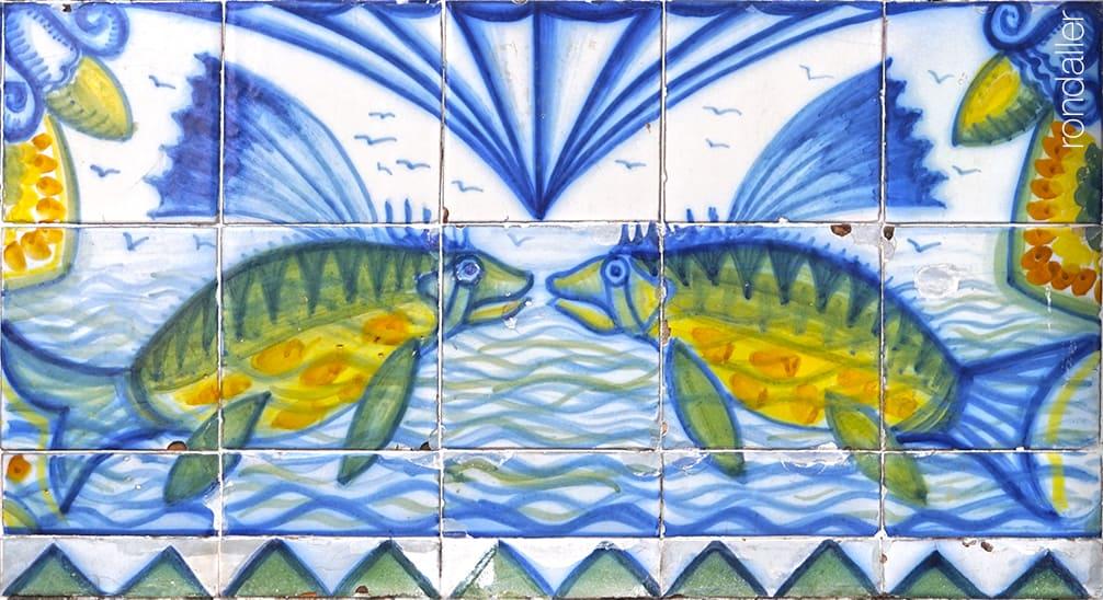 Detall del plafó ceràmic noucentista realitzat per Josep Aragay que representa dos peixos enfrontats.