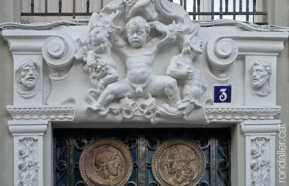 Conjunt escultòric en un portal on es veu un infant amb les cames obertes i diversos rostres.