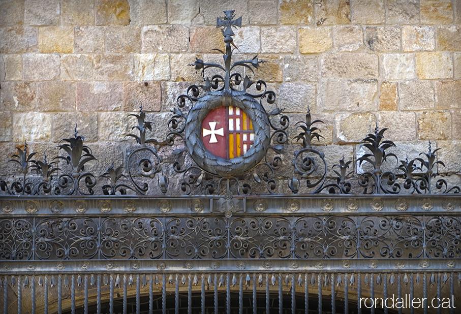 Hospital de la Santa Creu. Reixa de forja a la finestra de l'antiga farmàcia, amb l'escut de la Catedral i del Consell de Cent.