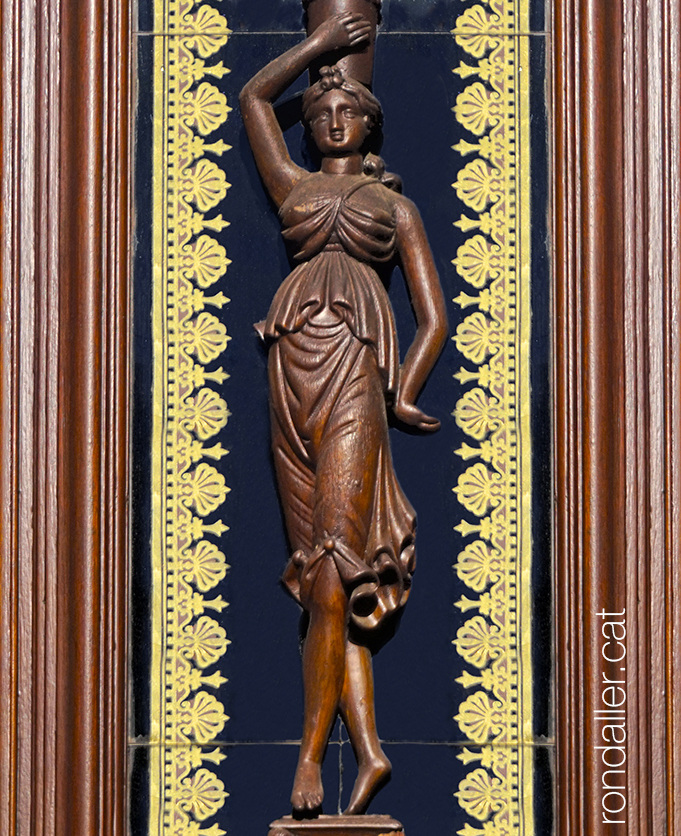 Escultura de fusta d'una estilitzada noia sostenint una gerra al cap, envoltada de sanefes i un marc.
