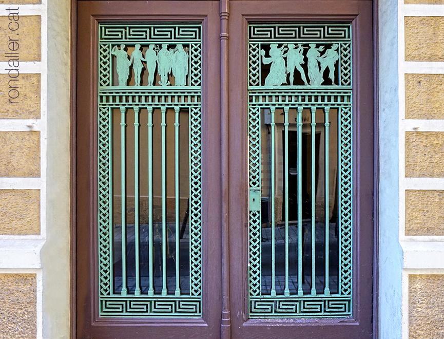 Porta noucentista al carrer Déu i Mata on, entre sanefes geomètriques hi ha personatges mitològics.