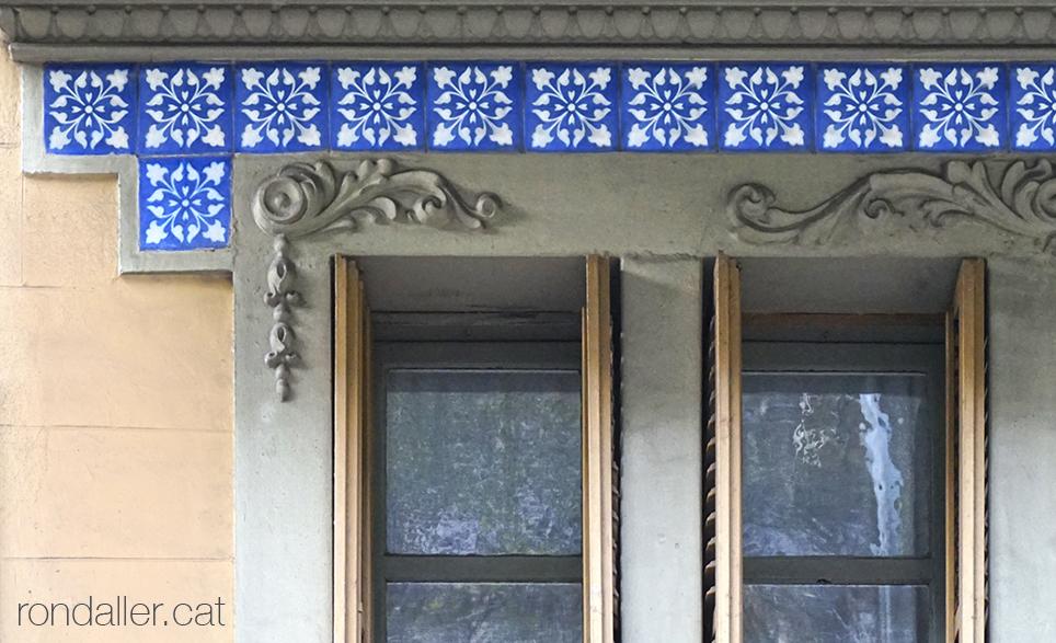 Fris de rajoles blaves emmarcant una finestra al carrer de la Diputació.