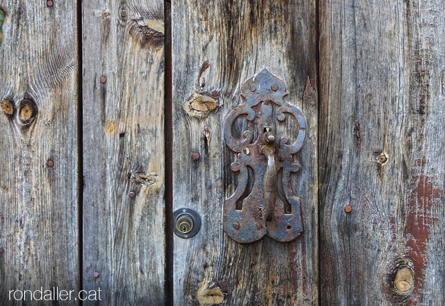 Picaporta de forja en una deslluïda porta de fusta d'aquesta poblacióde l'alta Cerdanya.
