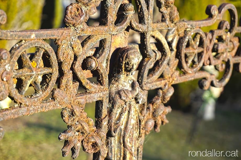 Creu de ferro damunt una tomba, amb la imatge de la Mare de Déu.