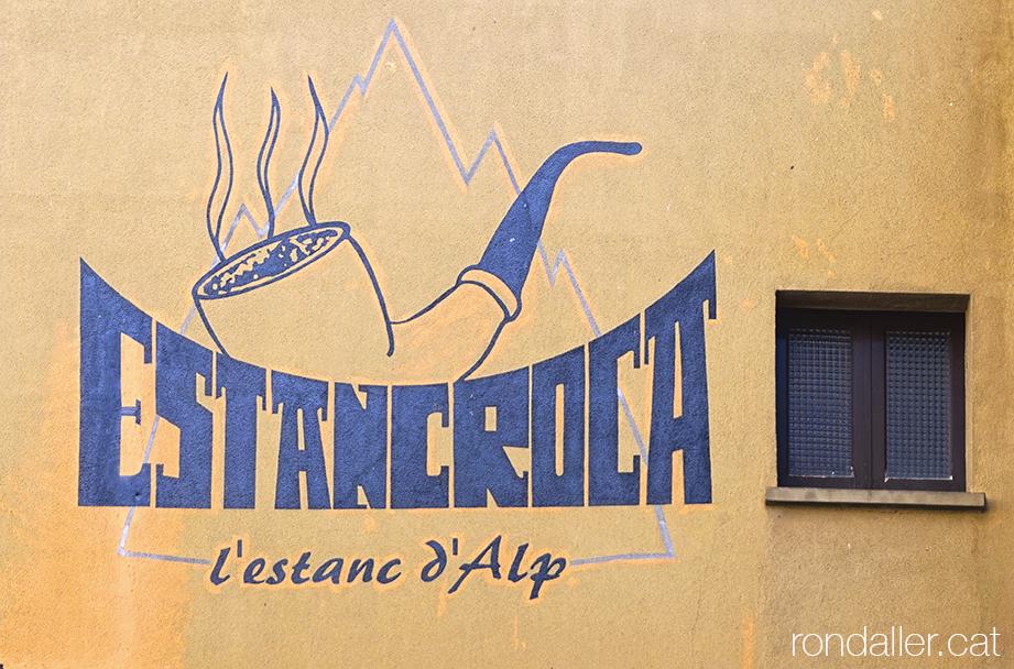 Rètol de l'Estanc Roca pintat a la façana de l'establiment al nucli antic d'Alp a la Baixa Cerdanya
