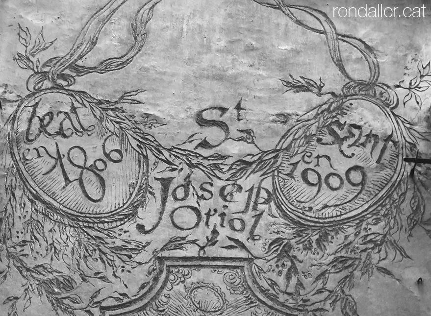 Detall de la decoració a la façana del carrer Mare de Déu del Pilar, amb el nom Sant Josep Oriol i les dates 1806 i 1909.