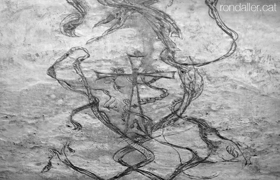 Detall dels esgrafiats de Jujol damunt el ciment, al barri de Sant Pere amb una creu i sanefes.