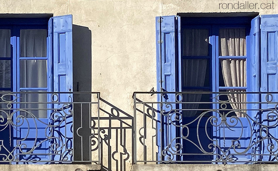 Dos balcons de forja amb les portes blaves al barri antic de La Tor de Querol a l'Alta Cerdanya.