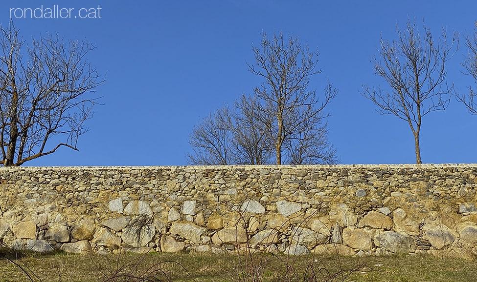 Mur de pedra que delimita uns camps de conreu a la vora del riu Querol o Aravó.