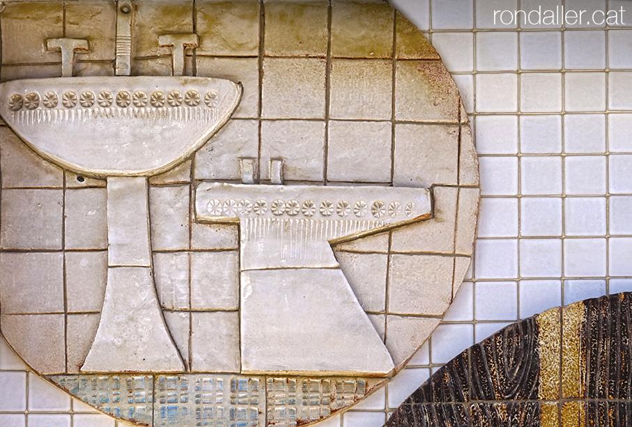 Mural ceràmic de Julio Bono amb un lavabo, a la façana d'una botiga d'Arenys de Mar.