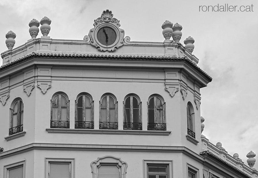Quart de Poblet. Edifici d'una antiga entitat bancària al carrer Major, amb un rellotge i gerres decoratives.
