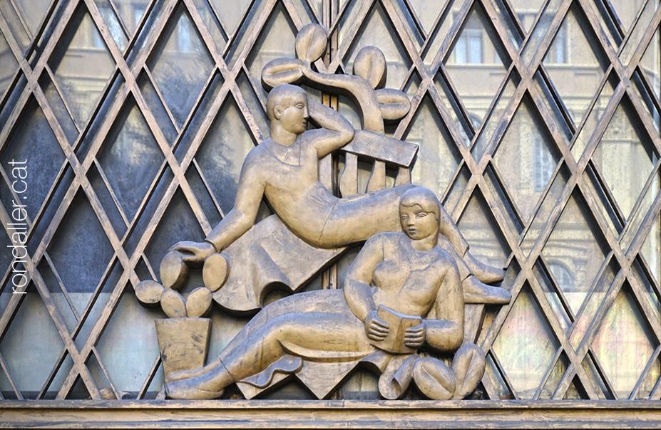 Casal de Sant Jordi. Relleu en metall en una porta, que representa una noia llegint i un noi assegut.