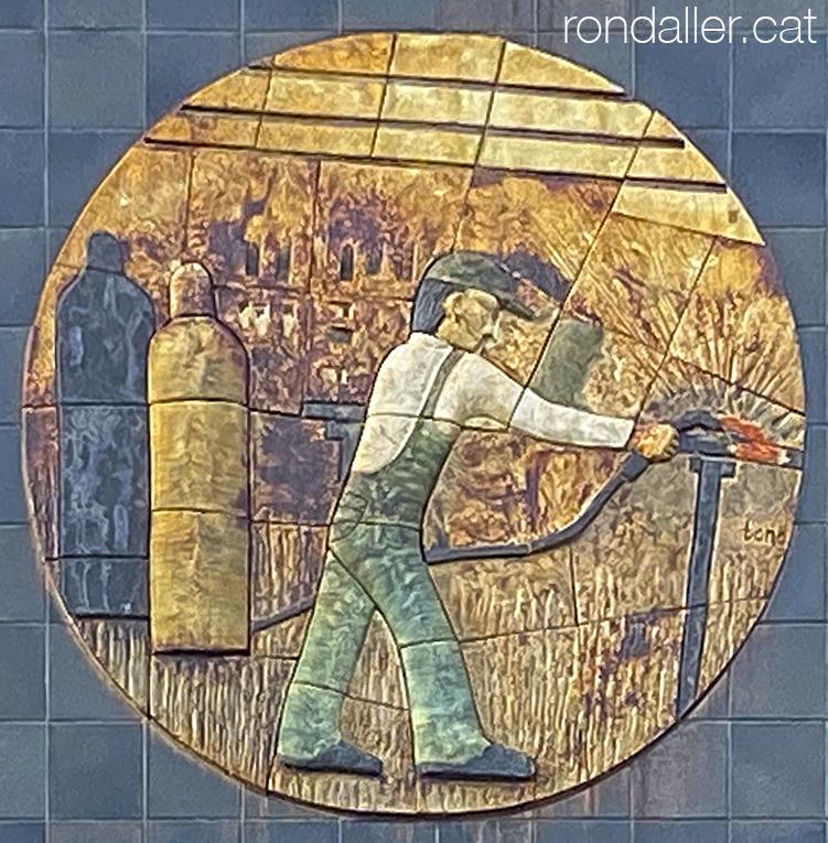 Obres de Julio Bono. Medalló de ceràmica on es veu un operari soldant en uns tallers de Mataró.
