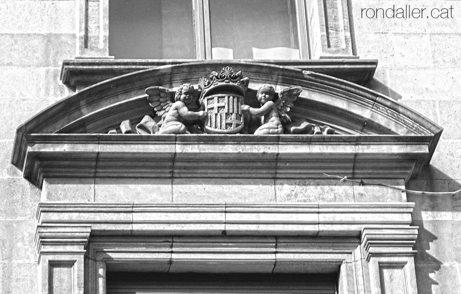 Finestra amb l'escut de Barcelona a l'antic edifici de l'Institut Nacional de Previsió.