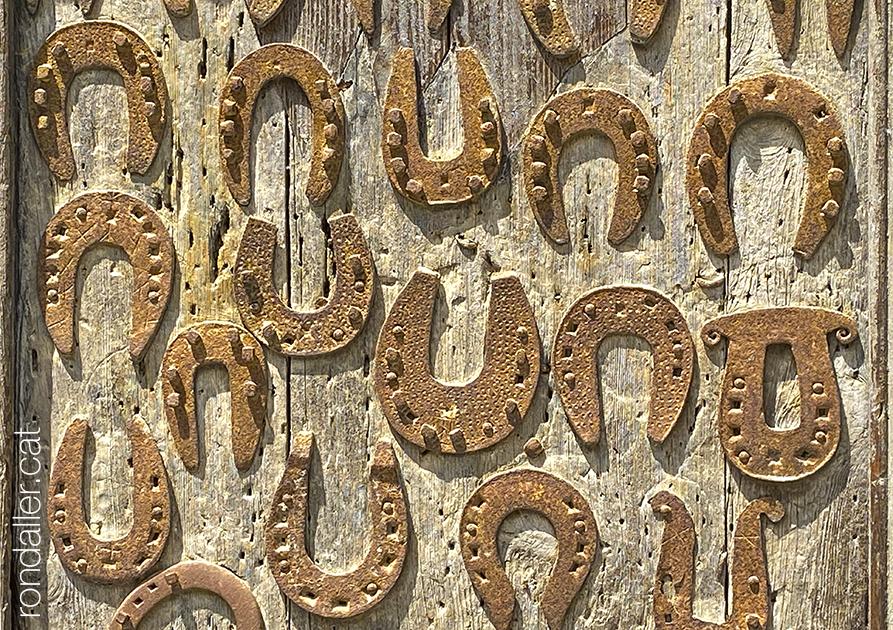 Detall de les ferradures clavades a la porta de l'església de Sant Martí d'Arenys de Munt.