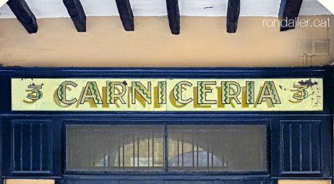 Rètol de vidre pintat en una carnisseria del carrer Prat de la Riba de Castelló d'Empúries.