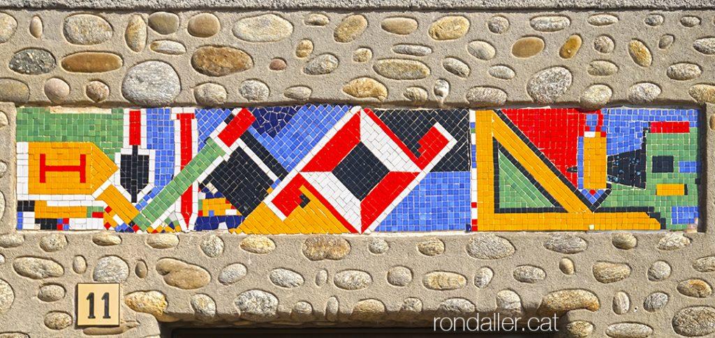Mosaic de tesel·les amb les eines de paleta a la llinda d'un edifici de L'Esquirol a Osona.
