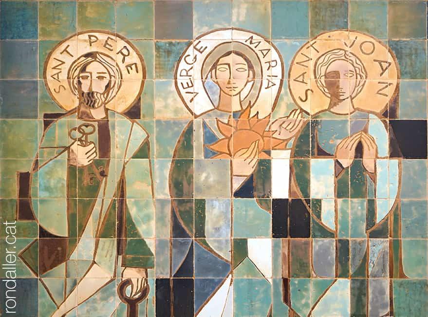 Obra realitzada a la façana el 1950 pel ceramista Enric Serra i Abella, que representa sant Pere, la Verge Maria i sant Joan.