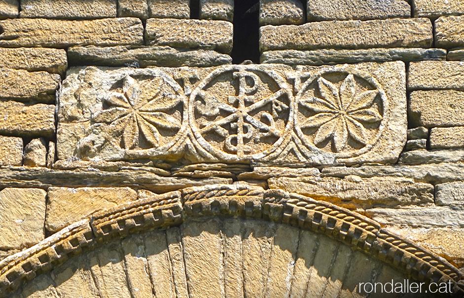 Església de Sant Fèlix de Vilac a la Vall d'Aran. Llosa amb el crismó dalt de la porta.