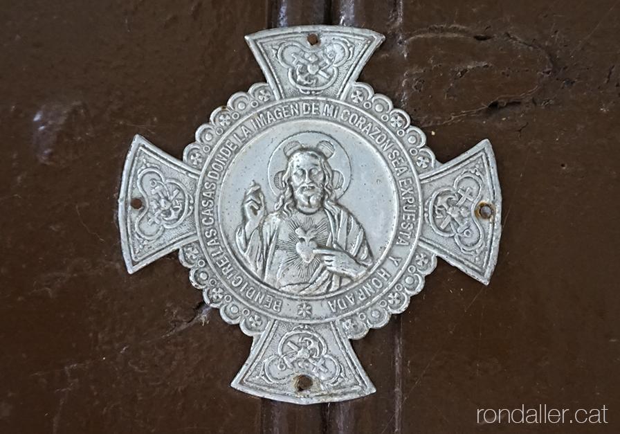 Placa amb la representació del Sagrat Cor en una porta d'Alàs (Alt Urgell).