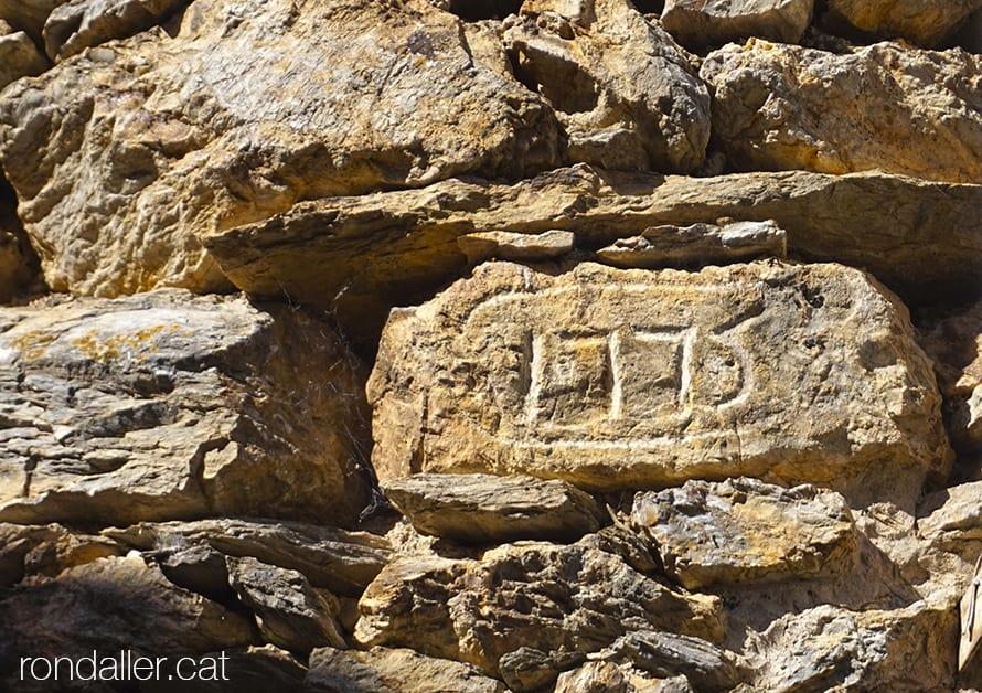 Pedra gravada amb l'any 1775 encastada en una paret. Urgellet. Alt Urgell.