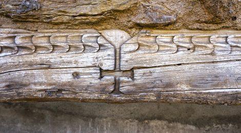 Biga de fusta amb un relleu encastada a la paret, a la vila d'Alàs a l'Urgellet (Alt Urgell).