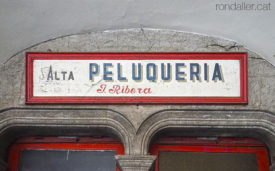 Rètol d'una antiga perruqueria sota els porxos de l'edifici de Cal Don Llorens.