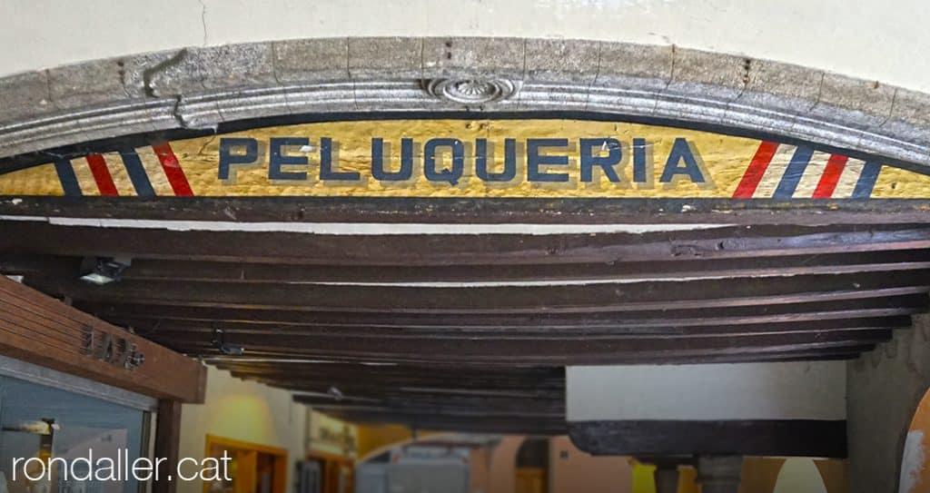 Rètol d'una perruqueria sota les porxades del carrer Major de la Seu d'Urgell.