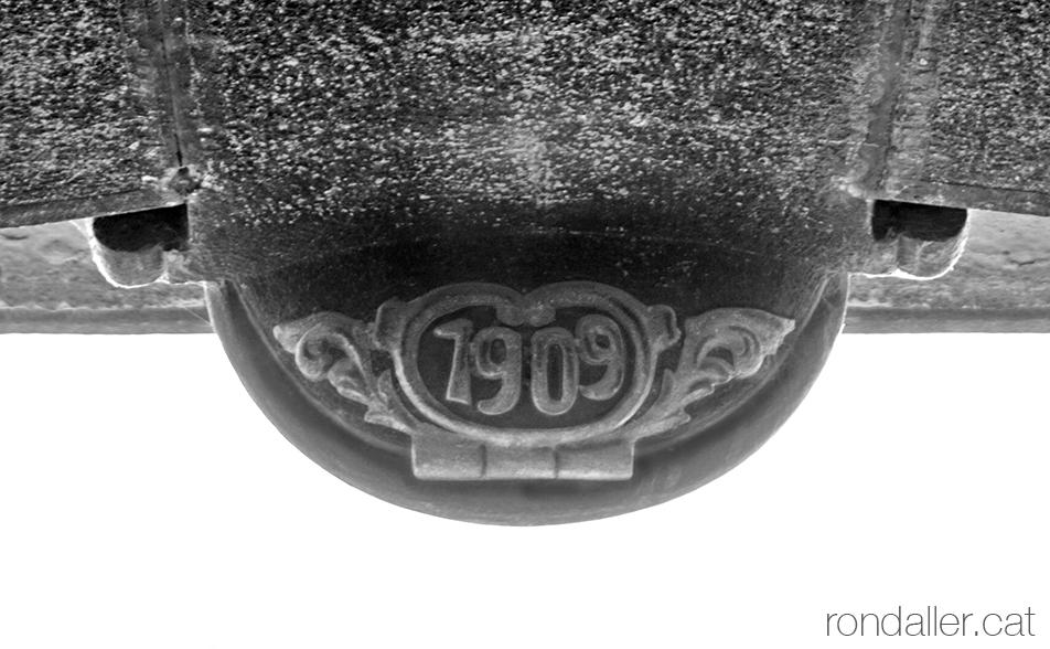 La data 1909 al rellotge de Can Girbal de Vic, en un dels porxos de la plaça Major o Mercadal.