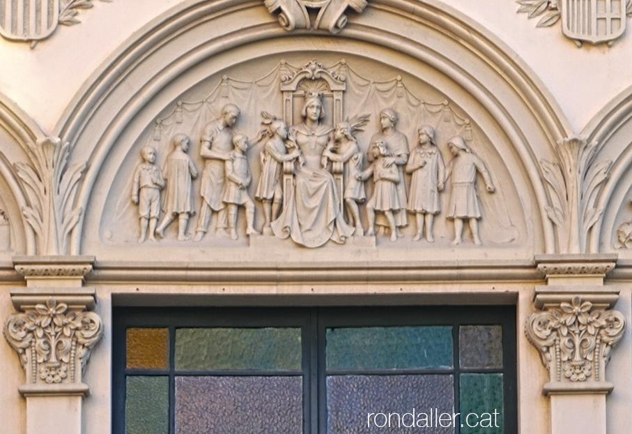 Timpà esculpit pels germans Llimona a l'entrada de les Escoles Ribas de Rubí, edifici projectat el 1916 per Emili Sala Cortés.