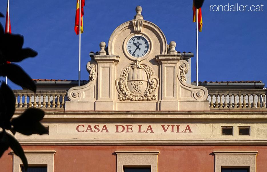 Coronament de l'edifici de l'Ajuntament de Rubí (Vallès Occidental), amb un rellotge i l'escut de la ciutat.
