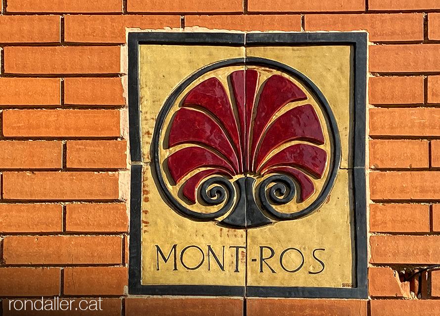 Placa de ceràmica amb el nom Mont-Ros i un motiu floral a la paret d'un bloc.