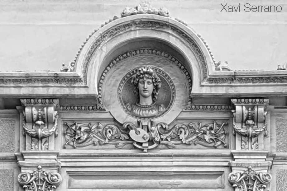 Casa Aleu o Casa Teresa Font de Barcelona. Frontó amb un bust femení i els atributs a la música i la pintura.