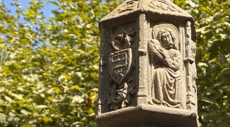 Detall dels relleus del tambor de la creu de terme de Tremp, obra gòtica del segle XVII, amb un escut i una figura.