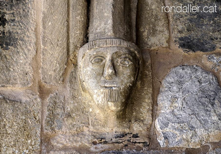Mènsula amb forma de cap escultòric a l'entrada del nàrtex de Gausac a la Vall d'Aran.