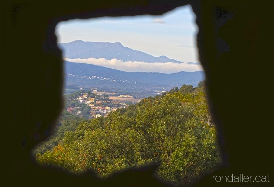 Panoràmica des d'una espitllera del castell, amb el massís del Montseny al fons.