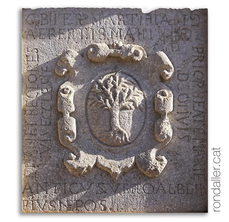 Llosa amb l'escut de Pineda de Mar (Maresme) amb una inscripció al voltant.
