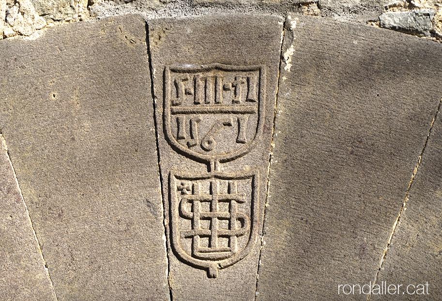 El monograma IHS a la porta de l'església de Sant Martí Sescorts, a Osona.