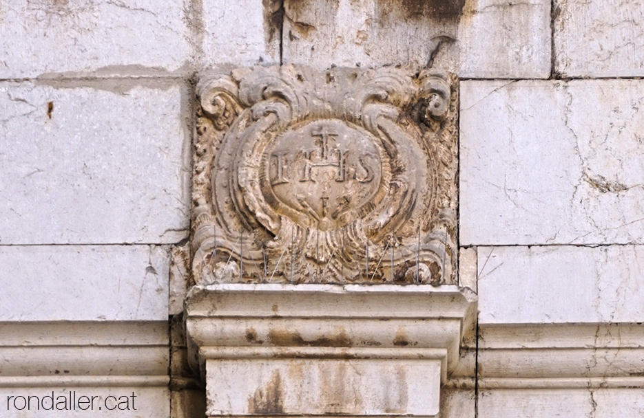 El monograma IHS a la porta lateral de l'església de Sant Antoni Abat de Vilanova i la Geltrú.