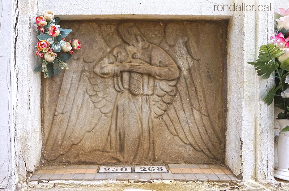 Relleu d'un àngel amb un infant en un nínxol del cementiri de Cabrera de Mar.