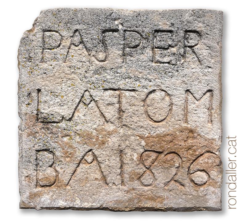 18 històries de Moià. Llosa funerària encastada al mur posterior de l'església parroquial.