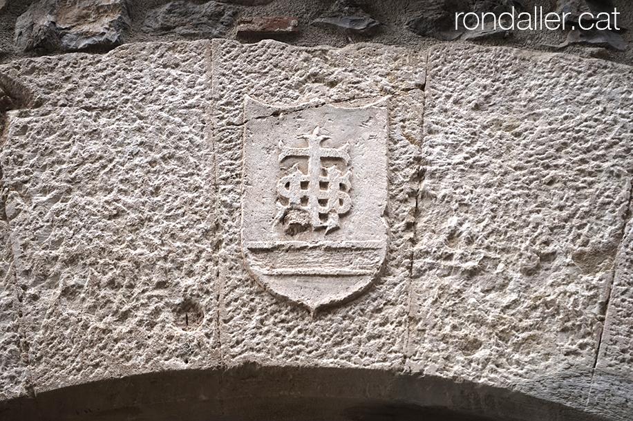 Dovella d'un portal amb el relleu de l'acrònim IHS i una creu.