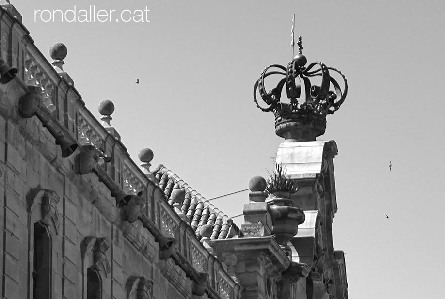 Coronament de la façana barroca amb la corona reial.