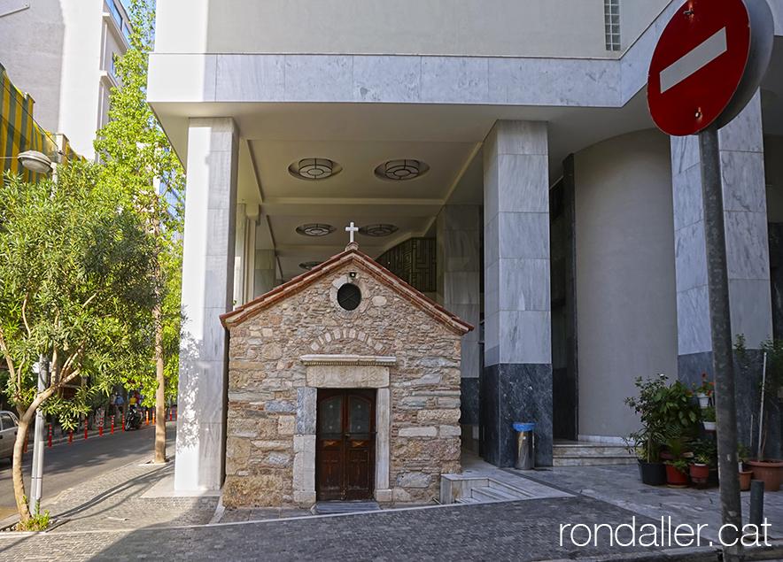 Petita capella al centre d'Atenes sota un bloc d'habitatges de recent construcció.